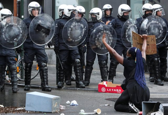 A demonstrator kneels while she holds up a sign in front of police officers during a protest, organised by Black Lives Matter Belgium, against racial inequality in the aftermath of the death in Minneapolis police custody of George Floyd, in central Brussels, Belgium on June 7, 2020. (Photo by Yves Herman/Reuters)