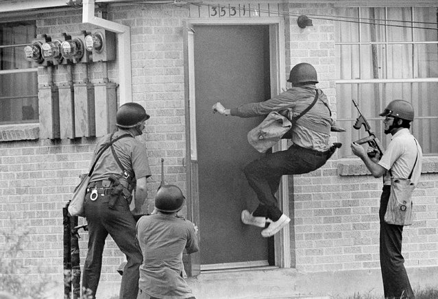 A policeman kick in the door of a residence next to the Black Panther headquarters in New Orleans as they moved in following a shootout, September 15, 1970. Other heavily armed policemen stand at ready. (Photo by Jack Thornell/AP Photo)