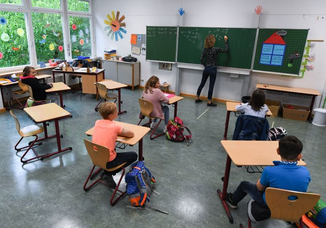 Students of class 4C of the Robert Schumann Primary School sit at a distance from each other in the classroom with their teacher Sylke Wassmann, on June 10, 2020 in Wiesbaden, Hessen, Germany. (Photo by Arne Dedert/picture alliance via Getty Images)