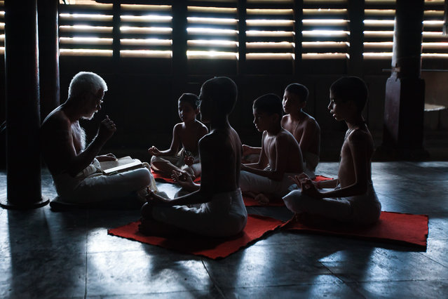 """""""Enlightenment"""". The teacher imparting ancient India scriptures, Rig Vedas to the students of the 400 year old Vedic Research Center of Kerala, one of the oldest in India. The teaching is done by traditional means of chanting and actions by hand and not by books. The students look at the the way the teacher is chanting and memorizes the method. The total year of learning is 4-1/2 years to complete the three Vedas. Photo location: Trissur, Kerala, India. (Photo and caption by Sreeranj Sreedhar/National Geographic Photo Contest)"""