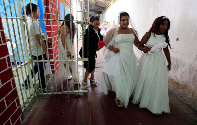 A woman in a wedding gown walks to a mass wedding ceremony, held 17 male inmates, in the Carcel Villa Hermosa prison in Cali, Colombia, August 19, 2016. (Photo by Jaime Saldarriaga/Reuters)
