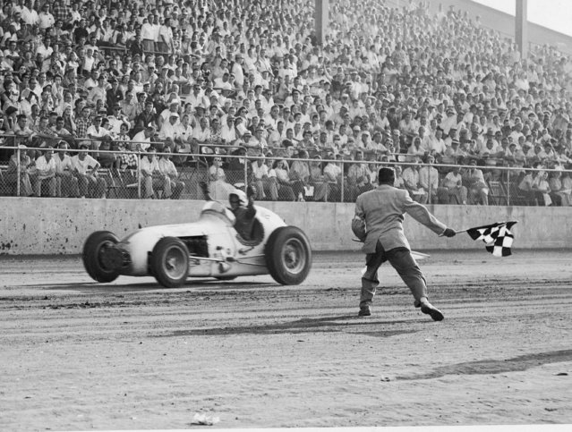 "Jimmy Bryan of Phoenix, Ariz., gets the checkered victory flag at the Indiana State Fairgrounds September 17, 1955 as he wins the ""Hoosier Hundred"" for the second consecutive year. Bryan averaged 83.98 miles an hour for the 100-lap, 100-mile AAA big car race. (Photo by AP Photo)"