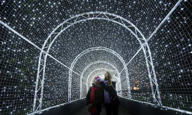 Visitors walk through a tunnel covered in lights, as part of an Christmas illuminated trail through Kew Gardens,  in London, Tuesday, November 21, 2017. (Photo by Frank Augstein/AP Photo)