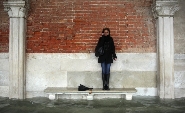 A woman stands on a bench above a flooded street during a period of seasonal high water in Venice November 11, 2012. The water level in the canal city rose to 149 cm (59 inches) above normal, according to the monitoring institute. (Photo by Manuel Silvestri/Reuters)