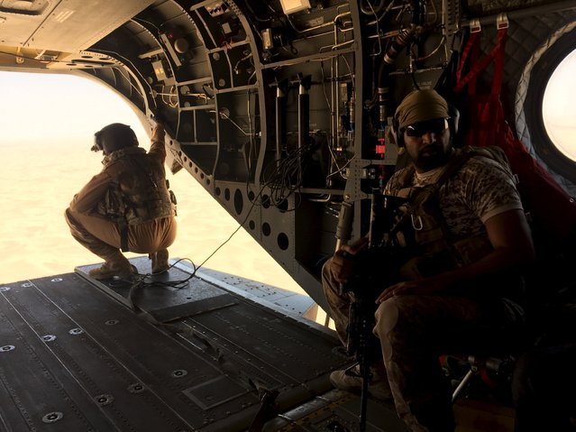 A soldier and an airman from the United Arab Emirates armed sit in a chinook helicopter flying a small group of journalists to the the frontline conflict zone of Marib in central Yemen September 14, 2015. (Photo by Noah Browning/Reuters)