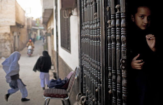 In this Thursday, November 15, 2012 file photo, a young girl peeks out from the barred entrance to her school waiting for her fellow students to arrive at Khushal School for Girls in Mingora, Swat Valley Pakistan. (Photo by Anja Niedringhaus/AP Photo)