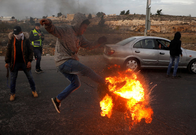 A Palestinian kicks a burning tire during clashes with Israeli troops at a protest against U.S. President Donald Trump's decision to recognize Jerusalem as Israel's capital, near the Jewish settlement of Beit El, near the West Bank city of Ramallah December 10, 2017. (Photo by Mohamad Torokman/Reuters)