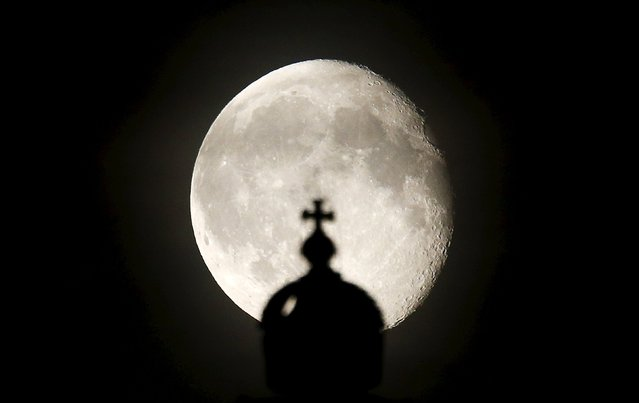 The moon rises next to a cross atop of the Reichstag building in Berlin, Germany, August 2, 2015. (Photo by Fabrizio Bensch/Reuters)