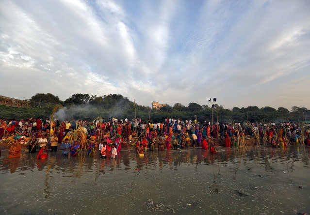 Hindu devotees gather to worship the Sun god Surya on the banks of the Sabarmati river during the Hindu religious festival of Chatt Puja in the western Indian city of Ahmedabad October 29, 2014. (Photo by Amit Dave/Reuters)