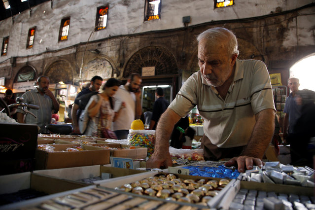 A man inspect sweets ahead of eid celebrations in al-Bazourieh Souk in Damascus, Syria September 10, 2016. (Photo by Omar Sanadiki/Reuters)