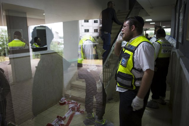 Israeli members of the Zaka Rescue and Recovery team are seen through a building's window as they work at the scene of a stabbing attack in the southern town of Kiryat Gat, Israel October 7, 2015. (Photo by Amir Cohen/Reuters)