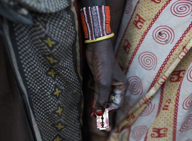 A Pokot woman holds a razor blade after performing a circumcision on four girls in a village about 80 kilometres from the town of Marigat in Baringo County, October 16, 2014. (Photo by Siegfried Modola/Reuters)
