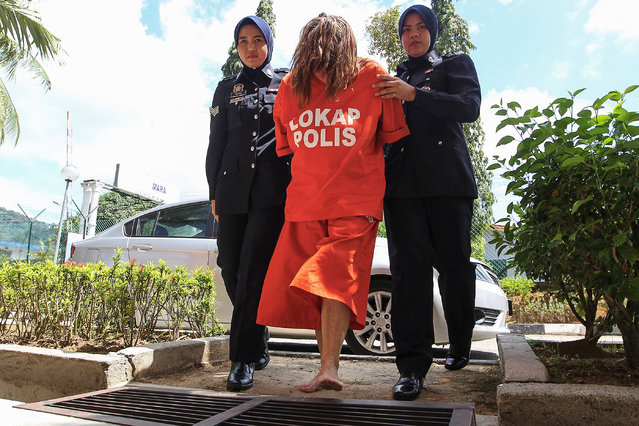 Brit woman Samantha Williams (C), 61, is escorted by a Royal Malaysian Police officer as they arrive at Langkawi court, state of Kedah, Malaysia, 30 October 2018. Samantha Williams has been arrested on 18 October for the alleged murder of her husband John William Jones, 62, who was found on the floor of their house with a stab wound to the chest with a kitchen knife in Malaysia. (Photo by EPA/EFE/Stringer)