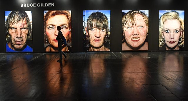 A visitor passes a street photography portraits series by US artist Bruce Gilden at an exhibition during the Photokina in Cologne, Germany, Tuesday, September 20, 2016. More than 1000 exhibitors from 51 countries show the latest developments in digital imaging until Sept. 25 at the Cologne fair halls. (Photo by Martin Meissner/AP Photo)