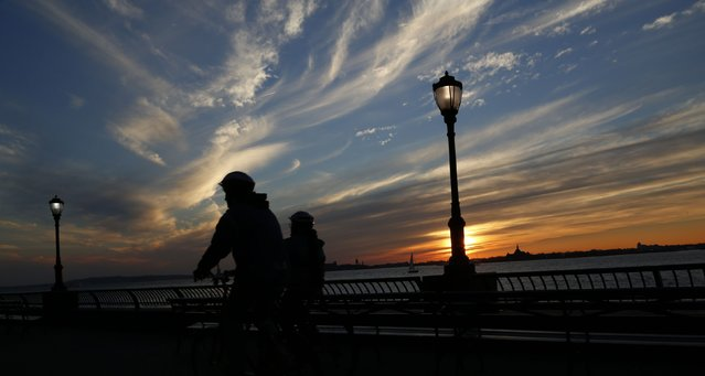 Cyclists are silhouetted as they ride in Battery Park at sunset alongside the Hudson River on an autumn day in New York November 9, 2014. (Photo by John Schults/Reuters)