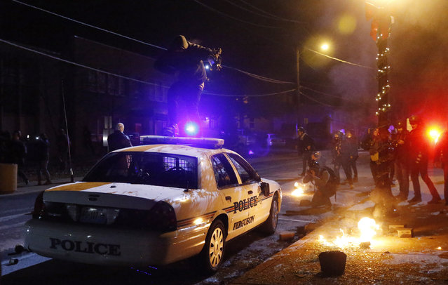 A protester jumps on a Ferguson police car set on fire by protesters in Ferguson, November 25, 2014. (Photo by Jim Young/Reuters)