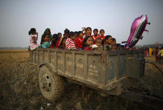 "Family and friends sit in a vehicle trailer, where they will spend the night, near the enclosure for buffalos awaiting sacrifice on the eve of the sacrificial ceremony for the ""Gadhimai Mela"" festival in Bariyapur November 27, 2014. (Photo by Navesh Chitrakar/Reuters)"