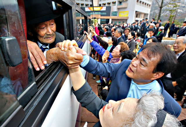 North Koreans (in the bus) grip hands of their South Korean relatives as they bid farewell after a separated family reunion meeting at the Mount Kumgang resort on the North's southeastern coast on October 22, 2015. North and South Korean families divided by war for more than 60 years said a final, traumatic farewell on October 22 after a reunion event that, for most, marked the last time they will ever see each other. (Photo by AFP Photo/Yonhap)
