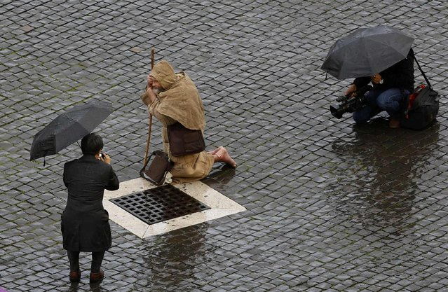 A man dressed as a monk kneels as he waits for the start of the conclave in Saint Peter's Square at the Vatican March 12, 2013. The doors of the Sistine Chapel shut on Tuesday, leaving 115 Roman Catholic cardinals inside to start a conclave to elect the next pope. (Photo by Max Rossi/Reuters)