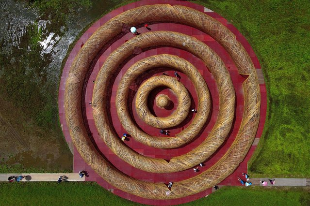 """An aerial view shows tourists visiting the bamboo-made art installation """"The ripple maze at Gaoshuang"""" by Taiwanese artist Lee Kuei-chih during the Art Land Festivals in Taoyuan on September 20, 2020. (Photo by Sam Yeh/AFP Photo)"""