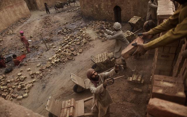 Pakistanis working in a brick factory in Mandra, near Rawalpindi, on March 20, 2013. (Photo by Muhammed Muheisen/AP Photo)