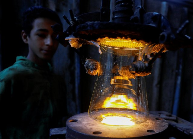 A boy works for 3$ per day during school vacation to assist his family, at a glass factory in Al Qalyubia Governorate, north of Cairo, Egypt on September 26, 2020. (Photo by Mohamed Abd El Ghany/Reuters)