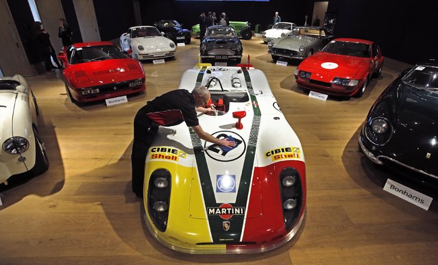 """Valeter Chris Bailey polishes a 1969-70 Porsche 908.02 """"Flunder"""" Langheck Group 6 Racing Sports Prototype at Bonhams auction house in London November 29, 2014. The vehicle is expected to achieve up to 3 million pounds ($ 4.5 million) when it comes to auction tomorrow. (Photo by Luke MacGregor/Reuters)"""