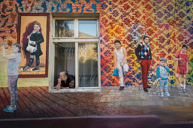 A resident smokes as she looks out from a window of a building with a mural painted in one of the courtyards in  Wroclaw, Poland, 28 October 2015. The painting, created by residents of neighbouring houses, is 250 meters long and covers 1,200 square meters of area. The work is a combination of painting, sculpture and ceramics made by residents of tenement houses as well by artists. The project is to revitalize the Nadodrze district in Wroclaw and activation of its residents. (Photo by Maciej Kulczynski/EPA)