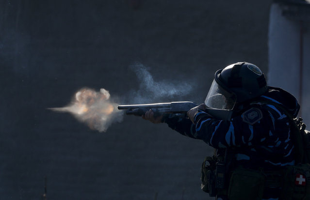 A police officer aims his weapon, as security forces fire tear gas and rubber bullets, during clashes with people after police broke up a squatters camp and evicted people living there in Guernica, Buenos Aires province, Argentina, Thursday, October 29, 2020. (Photo by Natacha Pisarenko/AP Photo)