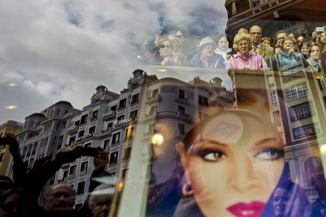 Mourners are reflected in a store window with a photograph of Sara Montiel, during her funeral in downtown Madrid, on April 9, 2013. Montiel, a famed, sultry-voiced Spanish actress who achieved Hollywood stardom, died Monday. She was 85. (Photo by Daniel Ochoa de Olza/Associated Press)