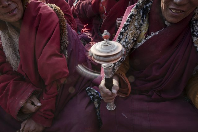 A Tibetan Buddhist monks spins a prayer wheel at Buddhist laymen lodge where thousands of people gather for daily chanting session during the Utmost Bliss Dharma Assembly, the last of the four Dharma assemblies at Larung Wuming Buddhist Institute in remote Sertar county, Garze Tibetan Autonomous Prefecture, Sichuan province, China October 31, 2015. (Photo by Damir Sagolj/Reuters)
