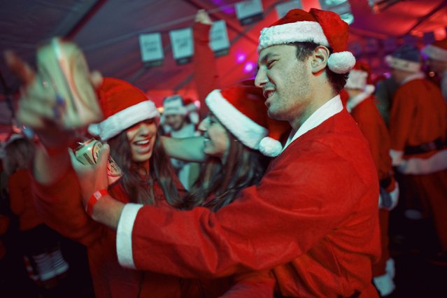 "(L-R) Eliza McGoldrick, 21, Valeruie Wilson, 21, and Jason Machellivi, 25, dance during an after-party for the ""Running of the Santas"" at the Electric Factory in Philadelphia, Pennsylvania December 13, 2014. (Photo by Mark Makela/Reuters)"