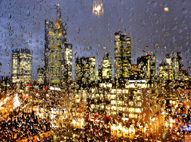 The buildings of the banking district are seen through thousands of rain drops on a glass railing in central Frankfurt, Germany, Wednesday, January 11, 2017. (Photo by Michael Probst/AP Photo)