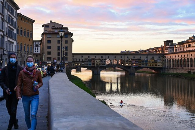People walk at twilight along the Arno river near the Ponte Vecchio in downtown Florence, Tuscany, on November 14, 2020 during the COVID-19 pandemic caused by the novel coronavirus. The Italian government imposed tighter restrictions on another five regions on November 10, including Tuscany, as it tries to stem escalating new cases of coronavirus, while still resisting a nationwide lockdown. (Photo by Vincenzo Pinto/AFP Photo)