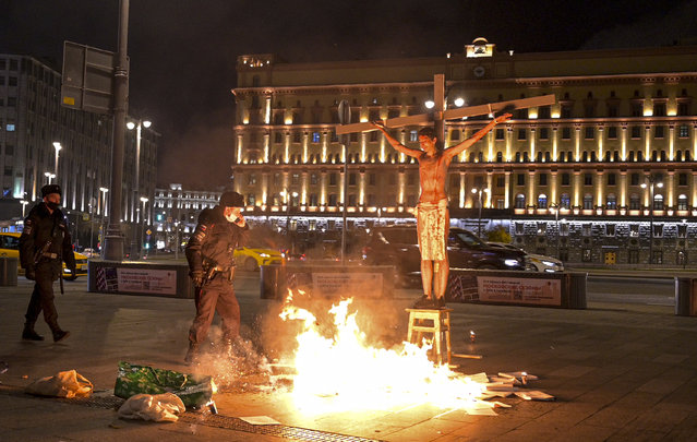 A police officer speaks on the phone as Russian activist Pavel Krisevich poses on a cross with the headquarters of the Federal Security Service (FSB) seen in the background in Moscow, Russia, Thursday, November 5, 2020. Krisevich's associates doused the pavement with a liquid harmlessly burning at a low temperature during the action, intended to draw public attention to what they describe as the FSB's alleged involvement in efforts to stifle dissent. (Photo by George Markov/AP Photo)