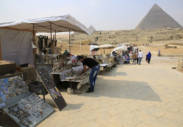 Souvenir vendors wait for tourists in front of the Giza pyramids on the outskirts of Cairo, Egypt, November 8, 2015. (Photo by Amr Abdallah Dalsh/Reuters)