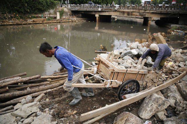 Labourers move stones to reinforce one of the city's many canals to help prevent flooding in central Jakarta October 28, 2014. Picture taken October 28, 2014. (Photo by Darren Whiteside/Reuters)