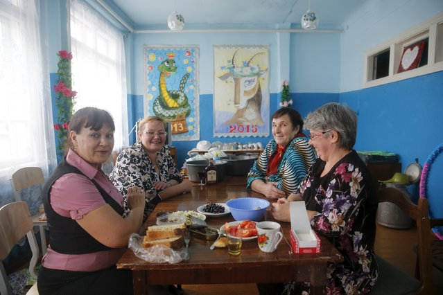 Local residents Elena, Olga, Galina and Tatiana drink and eat at the House of Culture in Sankin, Sverdlovsk region, Russia, October 17, 2015. (Photo by Maxim Zmeyev/Reuters)
