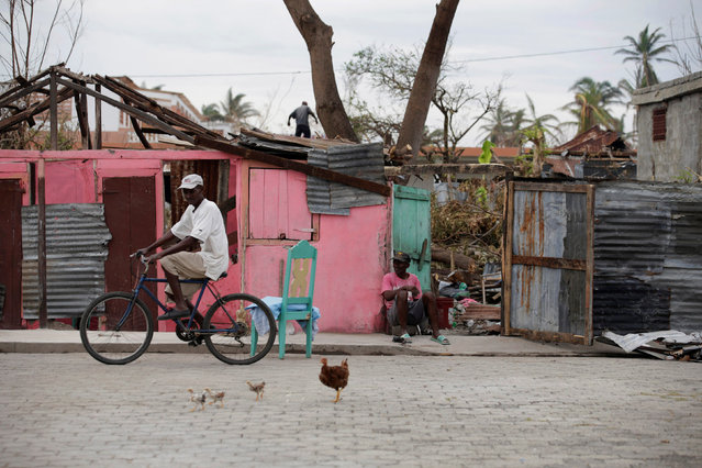 A man rides a bicycle next to a damaged house after Hurricane Matthew in Les Anglais, Haiti, October 14, 2016. (Photo by Andres Martinez Casares/Reuters)