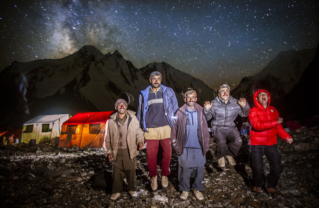 The porters photographed outside at base camp. They sometimes light fires using rubbish from the expeditions. (Photo by David Kaszlikowski/Rex Features)