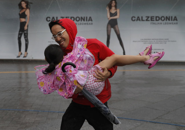 A man carries a girl brave the wind on the waterfront of Victoria Habour as Typhoon Haima approaches Hong Kong, Friday, October 21, 2016. (Photo by Vincent Yu/AP Photo)