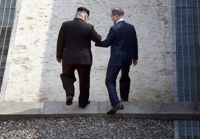 North Korean leader Kim Jong Un, left, and South Korean President Moon Jae-in cross the military demarcation line at the border village of Panmunjom in Demilitarized Zone Friday, April 27, 2018. Their discussions will be expected to focus on whether the North can be persuaded to give up its nuclear bombs. (Photo by Korea Summit Press Pool via AP Photo)