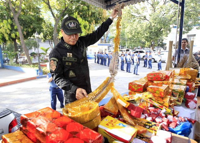 "A member of the Philippine National Police (PNP) Explosive Ordnance Disposal inspects some confiscated firecrackers locally name ""Judas Belt"" before a scheduled destruction of various prohibited firecrackers at a police station in Manila December 31, 2014. The government urged the public to refrain from using prohibited firecrackers and use alternative noise makers during the New Year revelry. Firecracker-related injuries has risen to 162 this year, the Philippine Department of Health reported on Tuesday. (Photo by Romeo Ranoco/Reuters)"