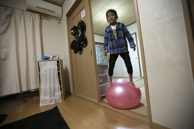 In this November 18, 2015 photo, 9-year-old Mahiro Takano, three-time Japan karate champion in her age group plays with a balance ball before going to her practice of karate at home in Nagaoka, Niigata Prefecture, north of Tokyo. (Photo by Eugene Hoshiko/AP Photo)
