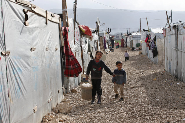 Syrian children walk between their tents at a refugee camp in Deir Zannoun village, Bekaa valley, Lebanon, Tuesday, January 6, 2015. (Photo by Hussein Malla/AP Photo)