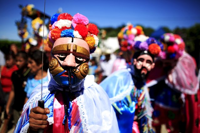 """Members of the traditional Los Historiantes dance group perform during a welcoming ceremony for Catholic devotees known as """"Cumpas"""", in the town of Cuishnahuat, El Salvador November 26, 2015. (Photo by Jose Cabezas/Reuters)"""