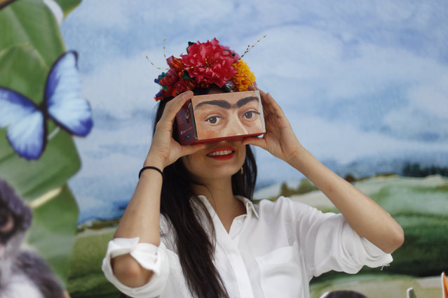 "A woman uses a virtual reality (VR) headset to view images by Mexican painter Frida Kahlo in Mexico City, Mexico, 23 May 2018. The technological giant Google launched the ""The Faces of Frida"", an interactive digital exhibition that treasures the heartrending work of the Mexican artist to tell her story from different points of view, with attention to the invisible details. (Photo by Sashenka Gutierrez/EPA/EFE)"