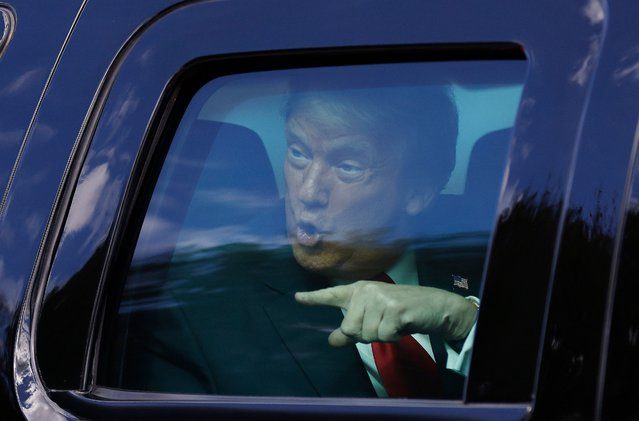 Outgoing US President Donald Trump waves to supporters lined along on the route to his Mar-a-Lago estate on January 20, 2021 in West Palm Beach, Florida. Trump, the first president in more than 150 years to refuse to attend his successor's inauguration, is expected to spend the final minutes of his presidency at his Mar-a-Lago estate in Florida. (Photo by Michael Reaves/Getty Images)