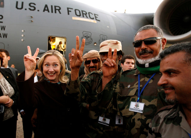 U.S. Secretary of State Hillary Clinton (C) gestures with Libyan soldiers upon her departure from Tripoli in Libya October 18, 2011. (Photo by Kevin Lamarque/Reuters)