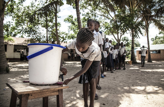 In this May 22, 2018 photo provided by UNICEF, schoolchildren wash their hands to help contain the Ebola outbreak before entering a classroom in the north-western city of Mbandaka, in Congo. Congo's health ministry announced six new confirmed Ebola cases and two new suspected cases Tuesday as vaccinations entered a second day in an effort to contain the deadly virus in the city of more than 1 million. (Photo by Mark Naftalin/UNICEF via AP Photo)